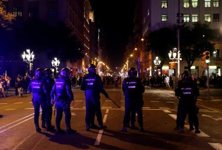 Riot police stand guard during a protest after a verdict in a trial over a banned independence referendum, in Barcelona