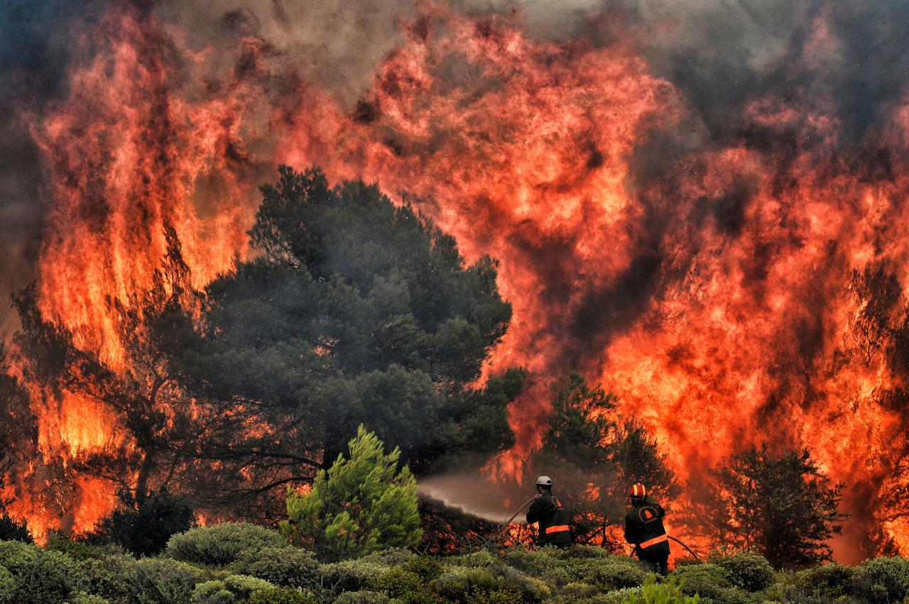 <p>Firefighters try to extinguish flames during a wildfire at the village of Kineta, near Athens, on July 24, 2018. Raging wildfires killed 74 people including small children in Greece, devouring homes and forests as terrified residents fled to the sea to escape the flames, authorities said Tuesday. (Photo from Valerie Gache/AFP/Getty Images) </p>