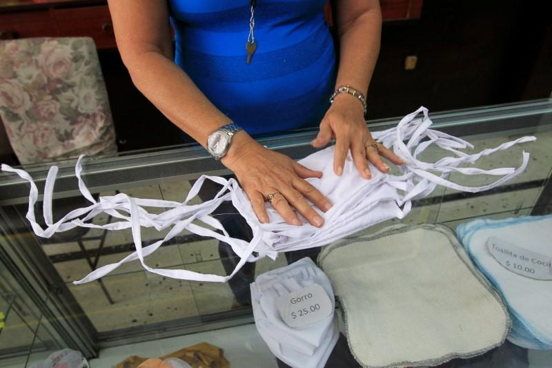A shopkeeper in a clothing store shows cloth face masks made in an adjoining workshop, in Havana
