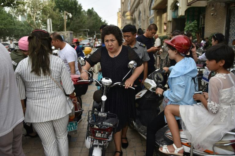 A Uighur woman pushes an electric bicycle in a crowded street in Kashgar in China's northwest Xinjiang region in June 2019