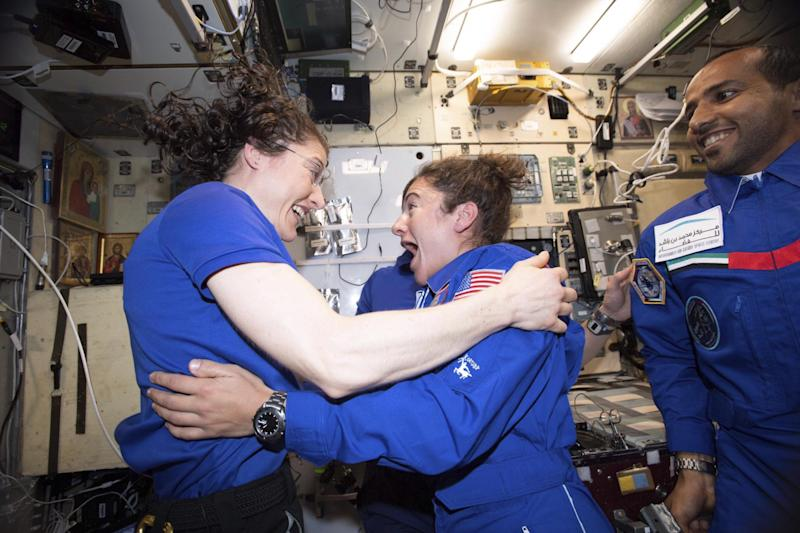 Christina Koch, left, and Jessica Meir greet each other on the International Space Station (AP)