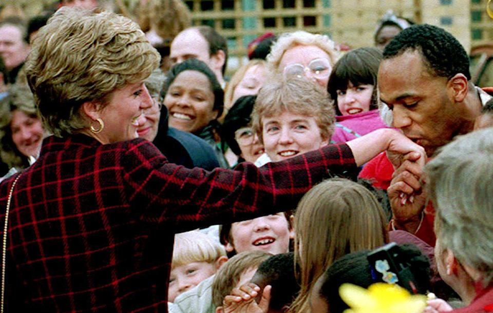 Princess Diana receives a kiss on the hand from trainee electrician Danny Walters, 29, during a walk in Southwark, South London 10 March 1993. (Photo credit should read EPA/AFP via Getty Images)