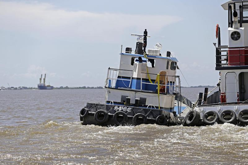 """C-Pec,"" the 47 foot tugboat which sank Saturday in the middle of the Mississippi River, is towed to dock after being raised from the depths of the river, and pumped of water, near Venice, La., Wednesday, July 10, 2013. (AP Photo/Gerald Herbert)"