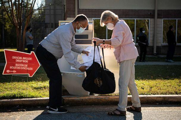PHOTO: Election officials collect ballots from a drop box on the last day of early voting in Georgia at the Lenora Park Gym in Snellville, Ga., Oct. 30, 2020.  (Tom Williams/CQ-Roll Call via Getty Images)
