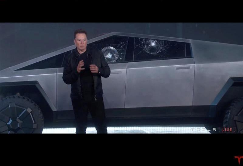 Tesla Chief Executive Elon Musk stands in front of the cracked windows of company's first electric pickup truck, the Cybertruck, after it was unveiled and a metal ball was thrown at the windows, in Los Angeles