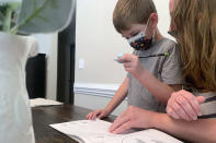 Five-year-old Berkeley Goss reviews class work with his mother, Emily, inside their Monroe, N.C. home on Monday, Sept. 13, 2021. Berkeley was forced to quarantine after a classmate tested positive for COVID-19 during the first week of in-person kindergarten. He was among seven thousand students to do so in the Union County School District where leaders have chosen not to require masks and end contact tracing. (AP Photo/Sarah Blake Morgan)