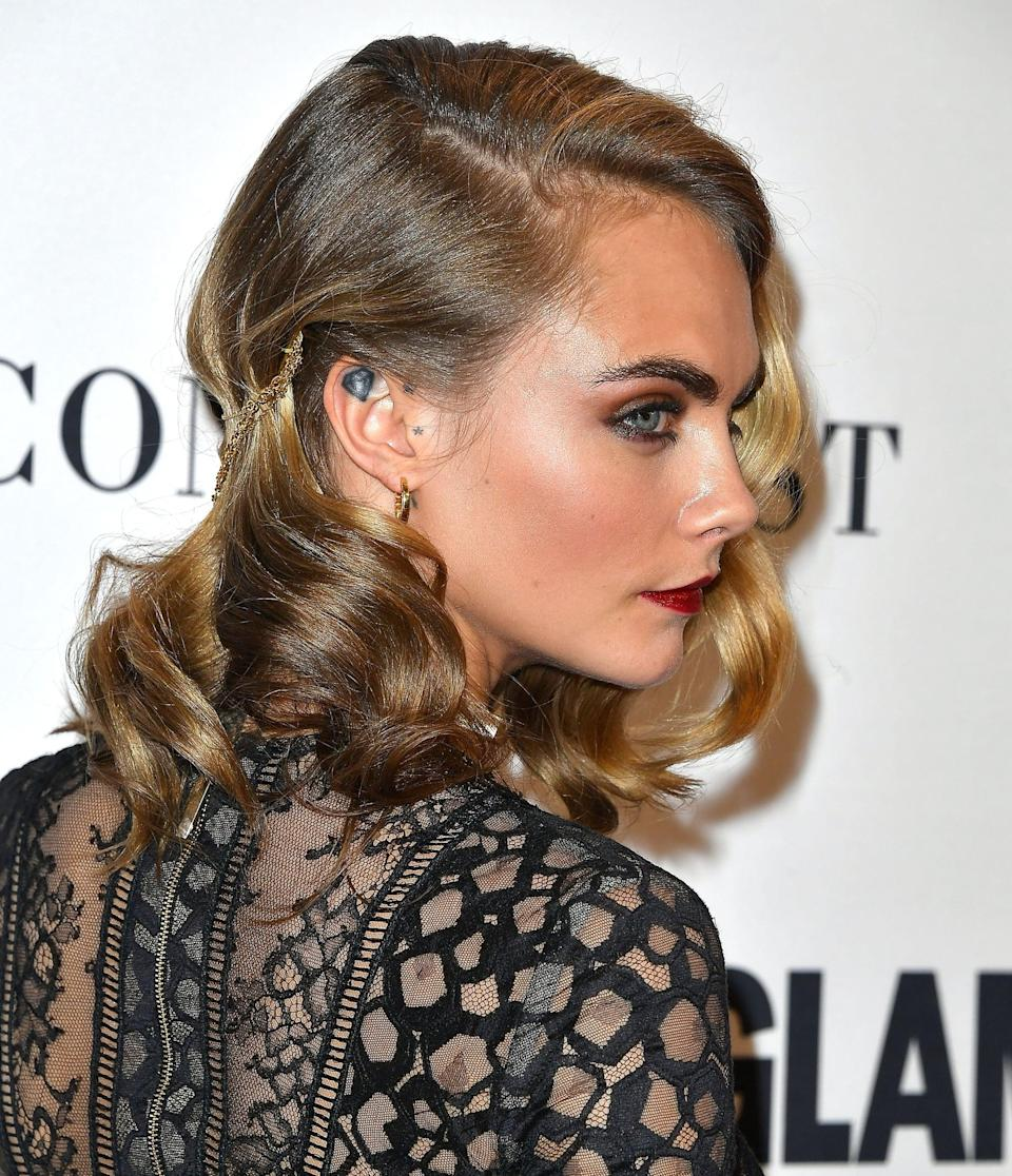 """<p>Look closely and you'll see Delevingne's gorgeous spirals feature a tiny, yet gorgeous, detail. For a red carpet event, <a href=""""https://www.youtube.com/watch?v=UyVjvLqfthM"""" class=""""link rapid-noclick-resp"""" rel=""""nofollow noopener"""" target=""""_blank"""" data-ylk=""""slk:Roszak draped a gold Jennifer Behr chain"""">Roszak draped a gold Jennifer Behr chain</a> across the back of Delevingne's hair, which was hidden enough not to take away from the entire look, but had just enough texture and shine to make things interesting.</p>"""
