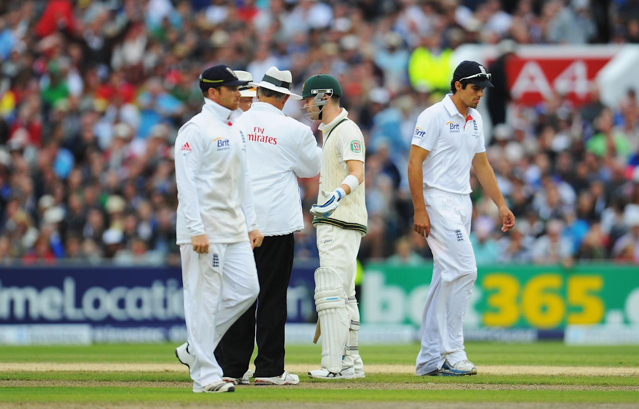 MANCHESTER, ENGLAND - AUGUST 04:  Michael Clarke of Australia talks to umpires Tony Hill and Marais Erasmus as Alastair Cook (R) of England walks off for bad light during day four of the 3rd Investec Ashes Test match between England and Australia at Emirates Old Trafford Cricket Ground on August 4, 2013 in Manchester, England.  (Photo by Stu Forster/Getty Images)