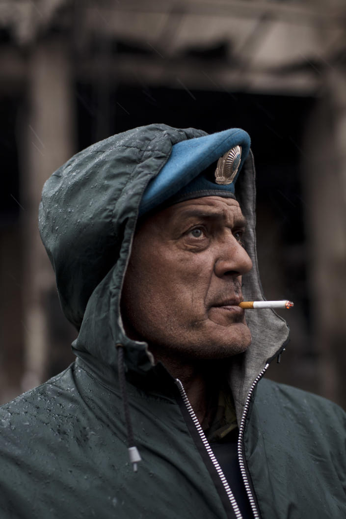 Dima, a member of a volunteer self defense group, smokes a cigarette during a rainfall in Kiev's Independence Square, Ukraine, Sunday, March 16, 2014. In a referendum watched closely around the world, residents in Ukraine's strategic Crimean Peninsula voted Sunday on whether to demand greater autonomy or split off and seek to join Russia. (AP Photo/David Azia)