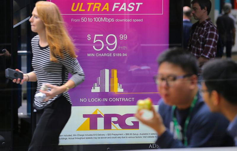 A woman looks at her phone as she walks past an advertisement for Australia's TPG Telecom Ltd in central Sydney, Australia