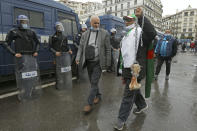 """A man holds a bone while shouting """"That's what's left for those who vote for the President"""" as Algerians demonstrate in Algiers to mark the second anniversary of the Hirak movement, Monday Feb. 22, 2021. February 22 marks the second anniversary of Hirak, the popular movement that led to the fall of Algerian President Abdelaziz Bouteflika. (AP Photo/Anis Belghoul)"""