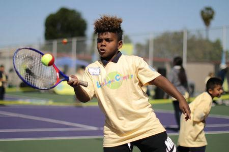 A boy hits a ball at a tennis workshop featuring U.S. Open Champion Sloane Stephens teaching tennis to 400 elementary students in Compton, California, U.S. April 12, 2018. REUTERS/Lucy Nicholson