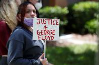 A protester holds a sign outside the Florida home of former Minneapolis police officer Derek Chauvin, in Orlando