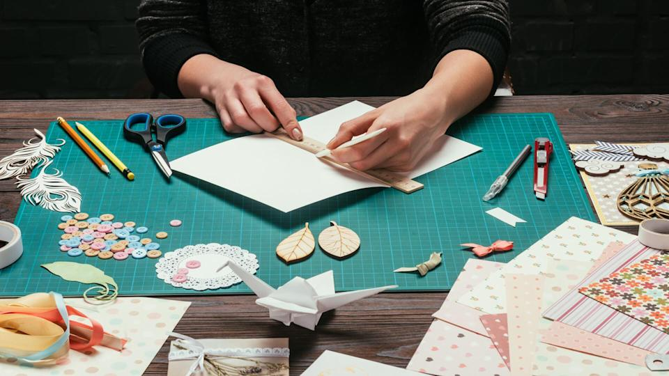 cropped image of designer cutting paper for scrapbooking greeting postcards.