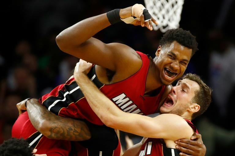 Hassan Whiteside (L) of the Miami Heat celebrates his buzzer beating game winning basket with teammate Goran Dragic while playing the Detroit Pistons, at the Palace of Auburn Hills in Michigan, on March 28, 2017