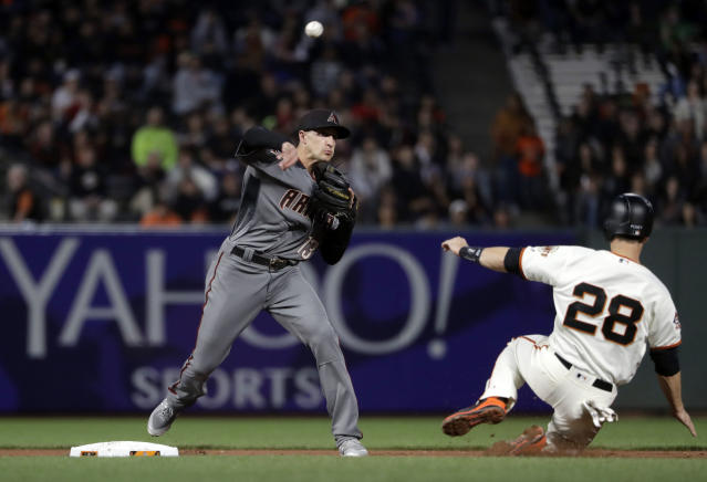 Arizona Diamondbacks shortstop Nick Ahmed, left, completes a double play over San Francisco Giants' Buster Posey (28) on a ground ball from Brandon Crawford during the second inning of a baseball game Monday, April 9, 2018, in San Francisco. (AP Photo/Marcio Jose Sanchez)