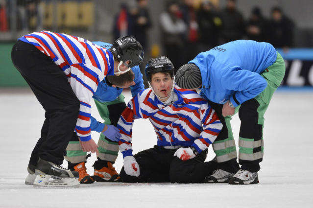 Injured referee Petri Kuusela is helped off the ice during the final match between Sweden and Russia at the Bandy World Championship in Vanersborg, February 3, 2013. Russian player Jevgenij Ivanusjkin collided with Kuusela. REUTERS/Anders Wiklund/Scanpix Sweden (SWEDEN - Tags: SPORT TPX IMAGES OF THE DAY) ATTENTION EDITORS - THIS IMAGE WAS PROVIDED BY A THIRD PARTY. NO COMMERCIAL SALES. SWEDEN OUT. NO COMMERCIAL OR EDITORIAL SALES IN SWEDEN. THIS PICTURE IS DISTRIBUTED EXACTLY AS RECEIVED BY REUTERS, AS A SERVICE TO CLIENTS - RTR3DB0C