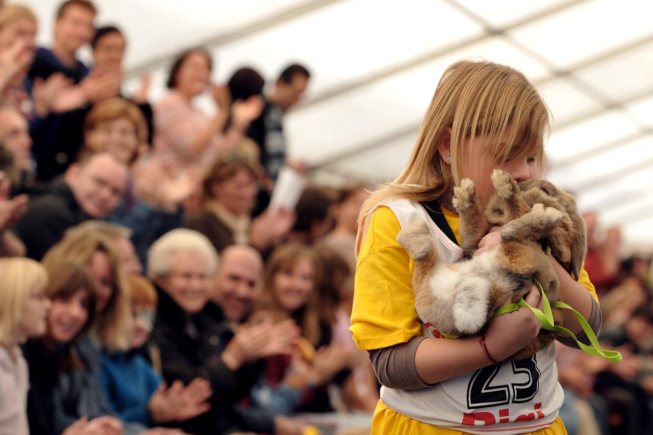 WOLLERAU, SWITZERLAND - OCTOBER 30:  A girl kisses her rabbit after an obstacle course during the first European rabbit hopping championships, which Lada Sipova-Krecova of Czech Republic won, on October 30, 2011 in Wollerau, Switzerland. Rabbit hopping is a growing trend among rabbit owners in Central Europe.  (Photo by Harold Cunningham/Getty Images)