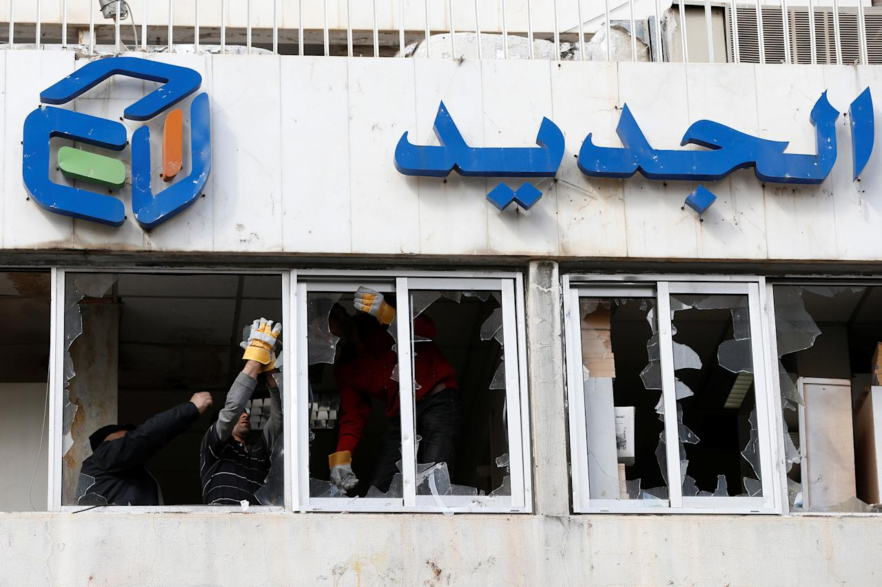 Workers remove broken glass from the headquarters of Lebanese television channel al-Jadeed, after demonstrators attacked the channel's headquarters on Tuesday, in Beirut, Lebanon February 15, 2017. REUTERS/Mohamed Azakir        TPX IMAGES OF THE DAY
