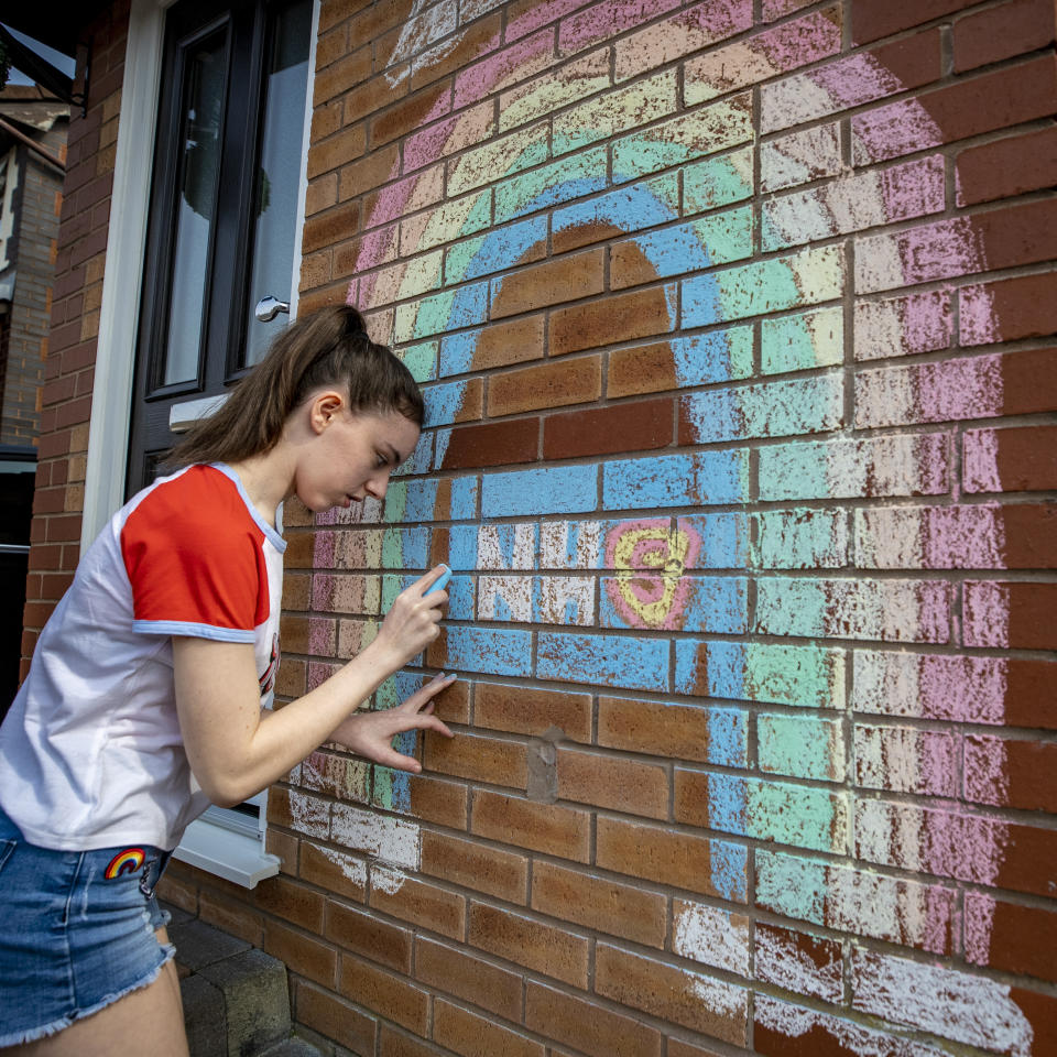 A teenager draws a rainbow and an NHS logo on the wall of her house in Liverpool in support of the NHS as the UK continues in lockdown to help curb the spread of the coronavirus.