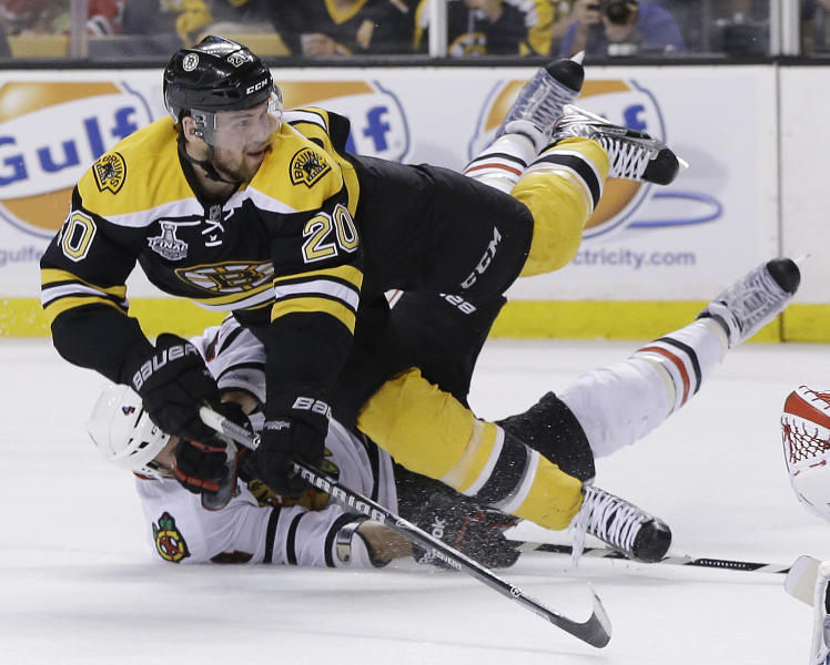 Chicago Blackhawks defenseman Niklas Hjalmarsson, bottom, of Sweden, takes down Boston Bruins left wing Daniel Paille (20) during the second period in Game 3 of the NHL hockey Stanley Cup Finals in Boston, Monday, June 17, 2013. The Bruins scored the game's second goal on the power play that followed. (AP Photo/Elise Amendola)