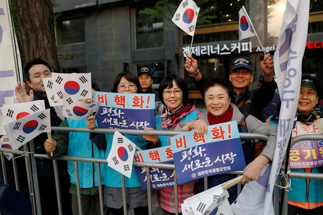 <p>Supporters hold South Korean flags and signs while waiting for a convoy transporting South Korean President Moon Jae-in to leave the Presidential Blue House for the inter-Korean summit, in Seoul, South Korea, April 27, 2018. (Photo: Jorge Silva/Reuters) </p>