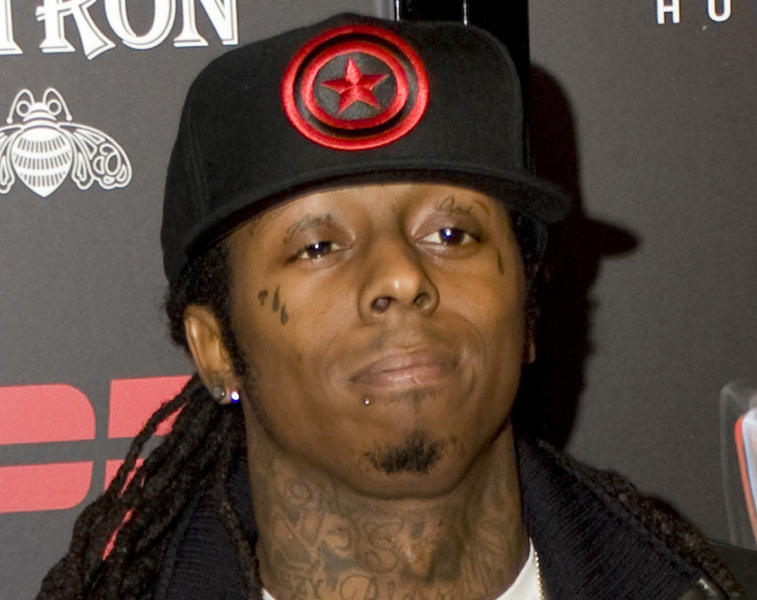 """FILE - In this Jan. 30, 2009 file photo, Rapper Lil Wayne arrives on the red carpet for the ESPN Next Big Weekend Super Bowl XLIII party in Tampa, Fla. Lil Wayne's management team on Friday, Oct. 26, 2012 said the rapper is on """"mandated rest"""" after a severe migraine and dehydration caused him to be hospitalized. (AP Photo/Steve Nesius, file)"""