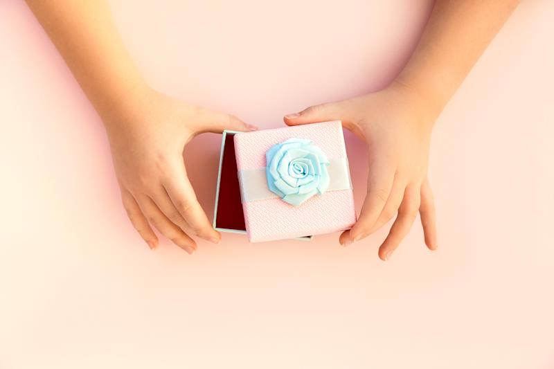 Hands of teenage girl holding a pink gift box with a blue satin ribbon on pastel background. View from above. Holiday concept of hand-made children's gifts for Valentines Day, Mother's Day, Christmas. Festive arrangement