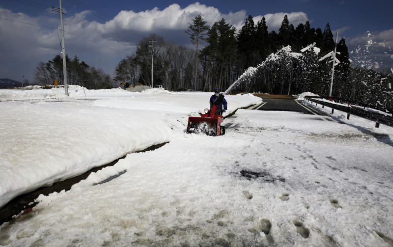 In this Monday, March 3, 2014 photo, a worker removes snow left on an access road at a construction site for housing March 11, 2011 tsunami survivors who lost their homes in Tanohata, Iwate Prefecture, northeastern Japan. In Tanohata, as in many other cities and towns laid waste by the mountain of water that scoured their scenic harbors, groundwork has just finished for a fraction of the many homes due to be built, with construction not yet started. (AP Photo/Junji Kurokawa)