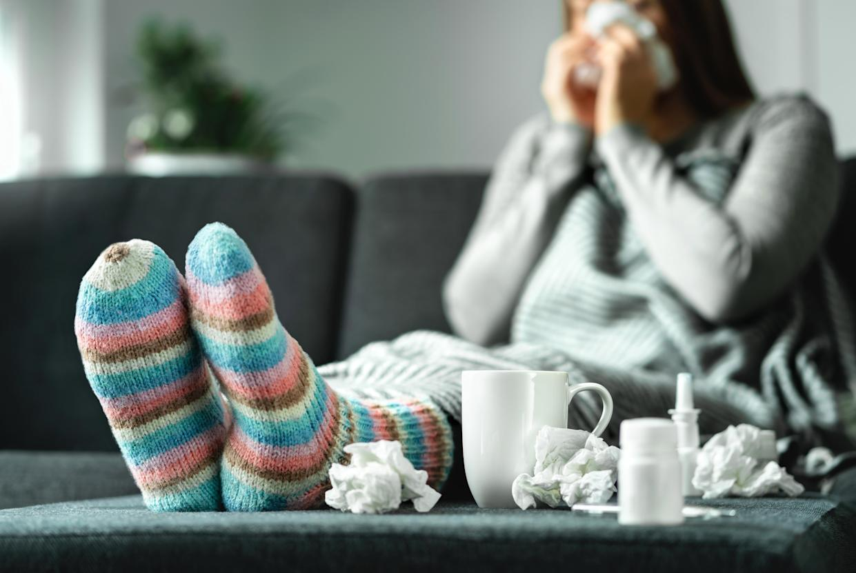 Sick woman with flu, cold, fever and cough sitting on couch at home. Ill person blowing nose and sneezing with tissue and handkerchief. Woolen socks and medicine. Infection in winter. Resting on sofa.