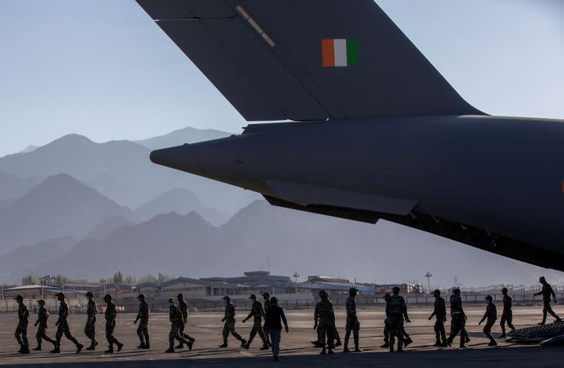 Indian soldiers disembark from a military transport plane at a forward airbase in Leh