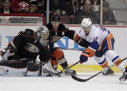 New York Islanders center Josh Bailey, right, tries to score against Anaheim Ducks goalie Jonas Hiller, left, as he is defended by Ducks' Saku Koivu, of Finland, during the second period of an NHL hockey game in Anaheim, Calif., Friday, Jan. 6, 2012. (AP Photo/Jae C. Hong)