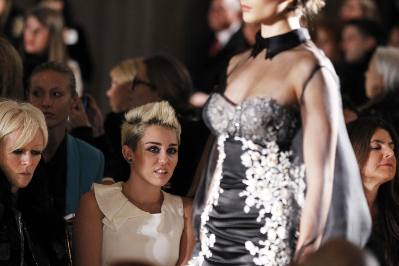 Singer Miley Cyrus watches a model presents a creation from the Marchesa Autumn/Winter 2013 collection during New York Fashion Week, February 13, 2013. REUTERS/Lucas Jackson (UNITED STATES - Tags: FASHION) - RTR3DRFS