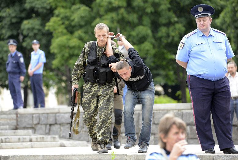 A pro-Russian militant detains a man suspected of spying for Ukraine in the eastern city of Donetsk, on June 21, 2014 (AFP Photo/Alexander Khudoteply)