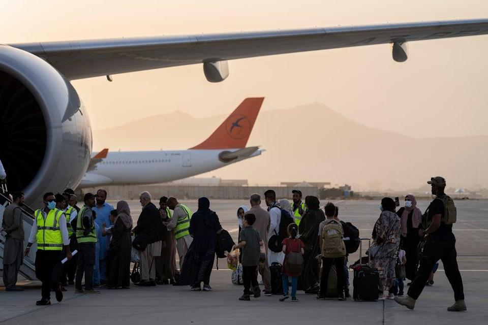 Foreigners board a Qatar Airways aircraft at the airport in Kabul, Afghanistan (AP)