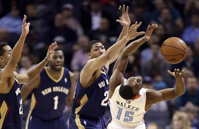 Charlotte Bobcats' Kemba Walker (15) stretches for the loose ball as New Orleans Pelicans' Brian Roberts, left, Tyreke Evans, middle, and Anthony Davis defend during the first half of an NBA basketball game in Charlotte, N.C., Friday, Feb. 21, 2014. (AP Photo/Bob Leverone)
