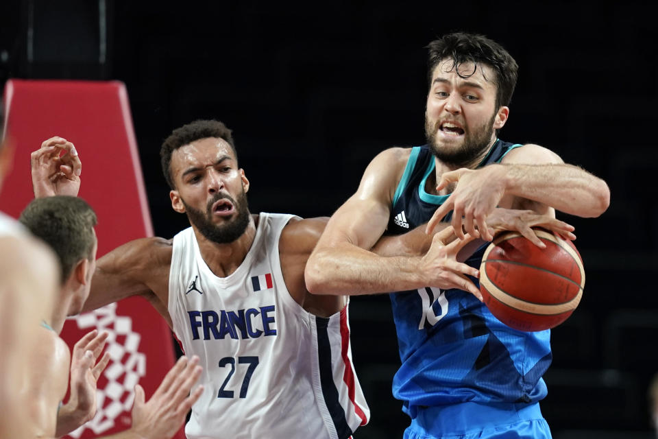 France's Rudy Gobert (27) fights for a rebound with Slovenia's Mike Tobey (10) during a men's basketball semifinal round game at the 2020 Summer Olympics, Thursday, Aug. 5, 2021, in Saitama, Japan. (AP Photo/Charlie Neibergall)