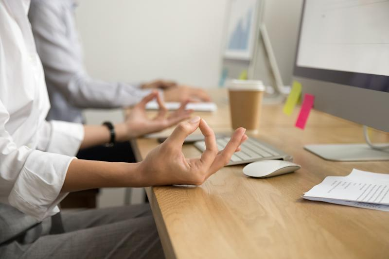 Office yoga for relaxation or concentration concept, calm businesswoman meditating at work, peaceful mindful employee practicing exercises at workplace, focus on female hands in mudra, close up view