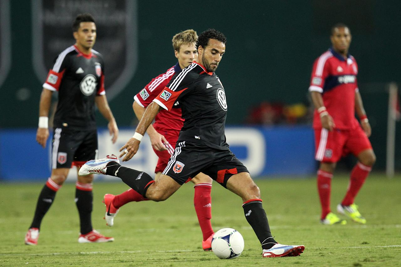 WASHINGTON, DC - AUGUST 4:  Dwayne De Rosario #7 of D.C. United passes the ball despite the attention of Chris Rolfe #18 of the Chicago Fire at RFK Stadium on August 22, 2012 in Washington, DC.(Photo by Ned Dishman/Getty Images)