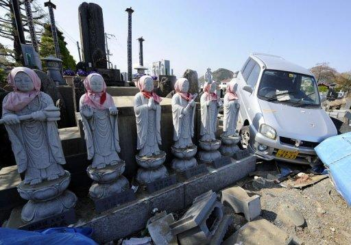 Photo taken on May 5 shows a vehicle sitting over tombstones at the graveyard of Kyudenji temple in the tsunami-devastated city of Ishinomaki, Miyagi prefecture. A year after whole neighbourhoods full of people were killed by the Japanese tsunami, rumours of ghosts swirl in Ishinomaki as the city struggles to come to terms with the awful tragedy