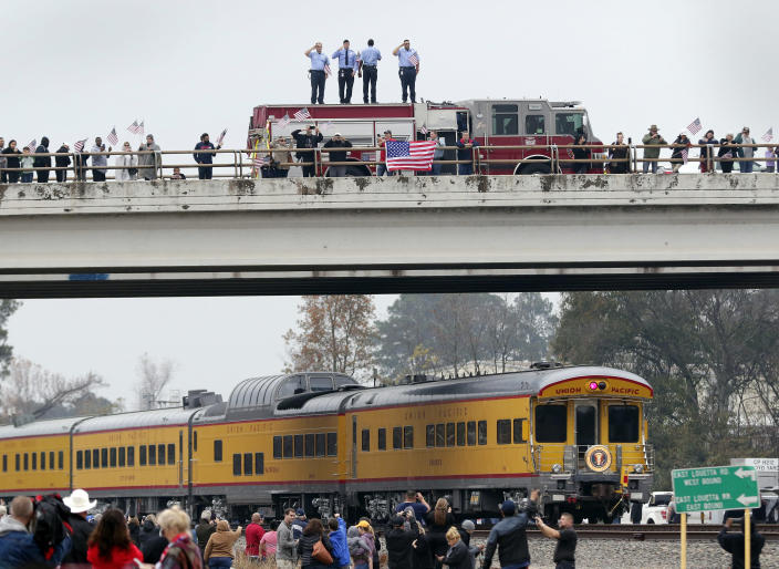 Firefighters stand on their truck and salute along with other attendants on an overpass as the train carrying the body of former president George H.W. Bush travels past on the way to Bush's final internment Thursday, Dec. 6, 2018, in Spring, Texas. (Photo: Michael Wyke/AP)