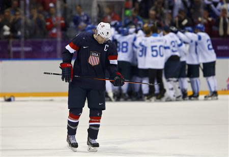 Team USA's Zach Parise skates away as Finland celebrates their win in their men's ice hockey bronze medal game at the Sochi 2014 Winter Olympic Games