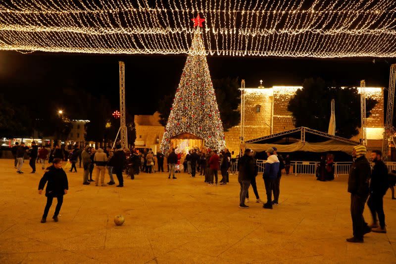 A girl plays with a ball as people stand at Manger Square in Bethlehem in the Israeli-occupied West Bank