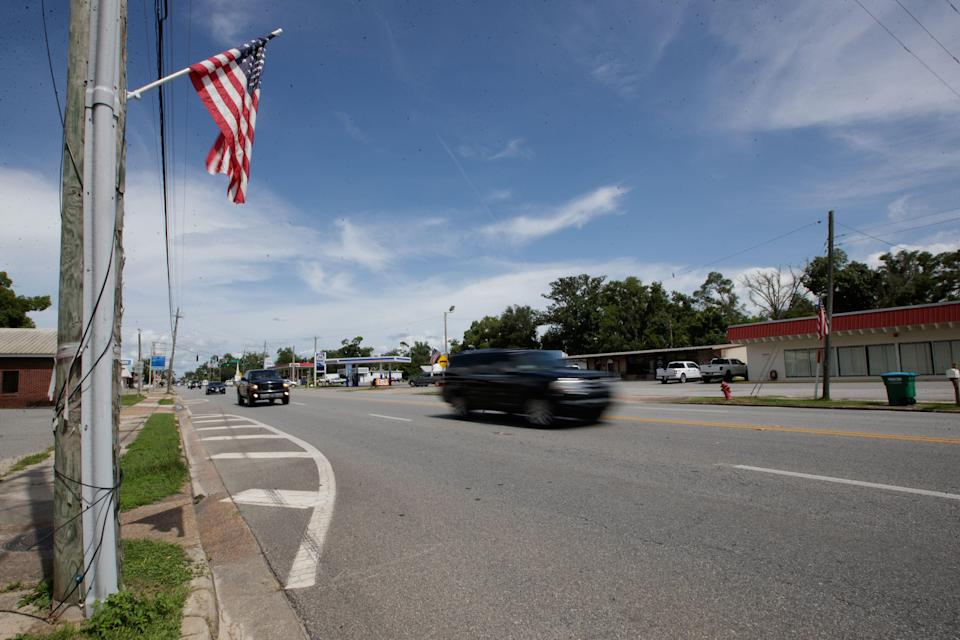 Cars pass by as American flags that line the highway in Blountstown, Florida fly in the wind Wednesday, July 21, 2021.