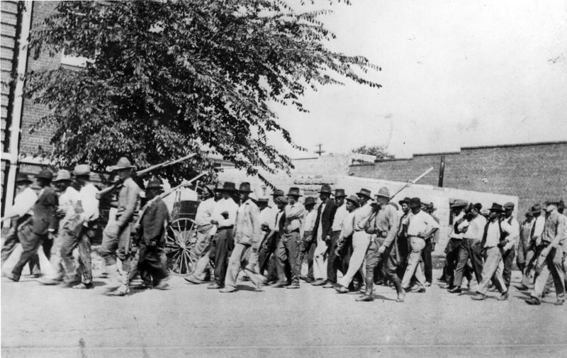 A group of National Guard Troops, carrying rifles with bayonets attached, escort unarmed African American men to the detention center at Convention Hall, after the Tulsa Race Massacre, Tulsa, Oklahoma, June 1921. (Oklahoma Historical Society/Getty Images)
