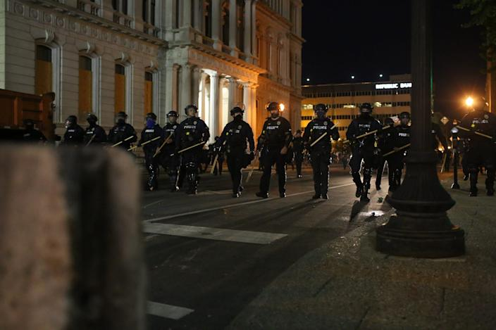 """A line of police officers march toward Jefferson Square Park in Louisville. <p class=""""copyright"""">Daniel Shular</p>"""