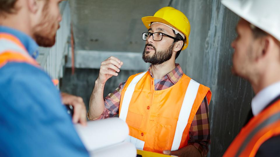 Portrait of bearded expert explaining construction details to workmen, making measurements as they go, all wearing reflective orange vests and hard hats.