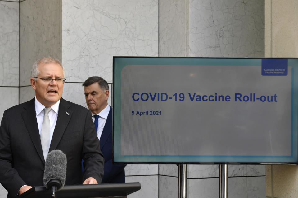 Australian Prime Minister Scott Morrison, left, addresses the media at a press conference as Department of Health Secretary Dr Brendan Murphy watches at Parliament House in Canberra, Australia, Friday, April 9, 2021. Australia says it has finalized a deal to buy an extra 20 million doses of the Pfizer vaccine as the nation rapidly pivots away from its earlier plan to rely mainly on the AstraZeneca vaccine. (Mick Tsikas/AAP Image via AP)