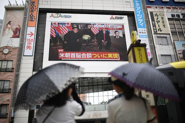 <p>In Tokyo, pedestrians watch live news of the meeting between North Korean leader Kim Jong Un and President Trump on Tuesday. (Photo: Martin Bureau/AFP/Getty Images) </p>