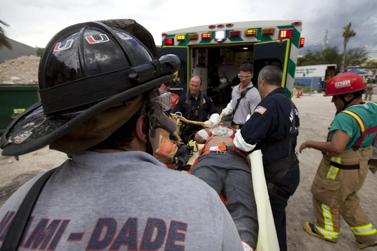 DORAL, FL - OCTOBER 10:  In this handout from Miami-Dade Fire Rescue, Miami-Dade Fire Rescue workers place an injured person into an ambulance after pulling him from under the rubble of a four-story parking garage that was under construction and collapsed at the Miami Dade College's West Campus on October 10, 2012 in Doral, Florida.  Early reports indicate that one person was killed, at least seven people injured and an unknown number of people may be buried in the rubble.  (Photo by Miami-Dade Fire Rescue via Getty Images)